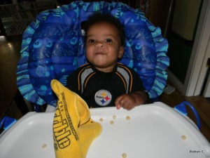 Cassie in her high chair with her Steelers outfit and Terrible Towel bib