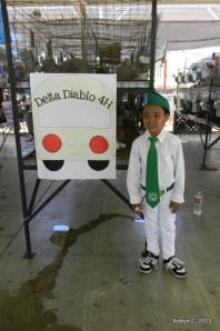 Jackson in his 4-H uniform in front of a poster