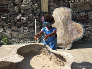 Cassie playing with bubbling mud at the Children's Museum